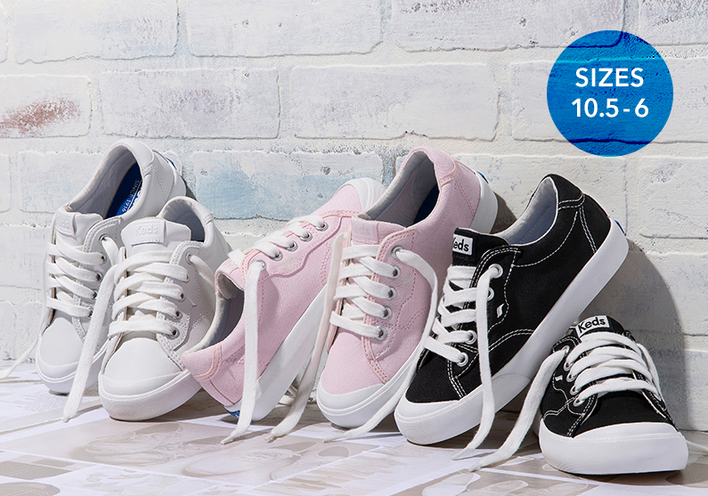 Pairs of Crew Kick 75 in white, pink and black lean up against a whitewashed wall.
