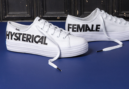 White Keds with contrasting large, all-caps black type down the sides. The word HYSTERICAL on one shoe and FEMALE on the other.