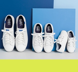 3 pair of Ked's sneakers lined up from big to small.