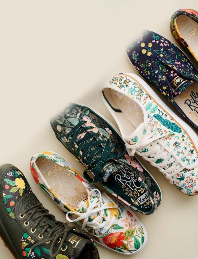 A row of Rifle Paper Co. Keds shoes and boots.