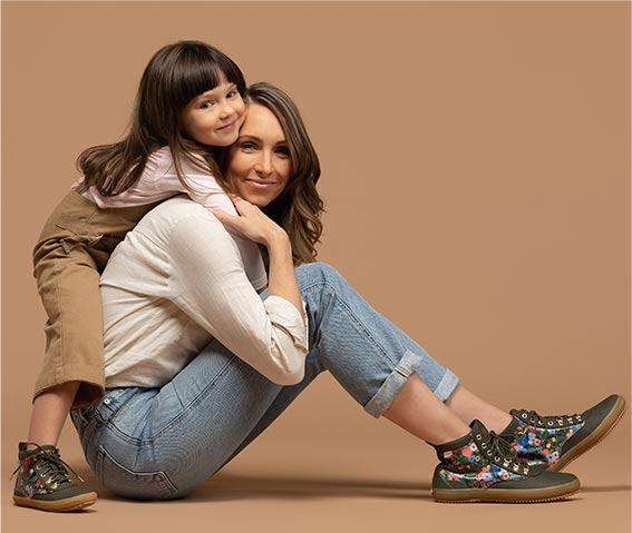 A girl hugging the back of a Woman sitting on the floor with matching Keds shoes.