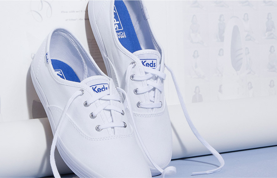 Keds CHampion Sneaker leaning untied against a wall.