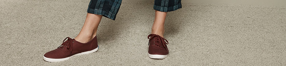 Close up of a pair of Keds on the feet of a person.