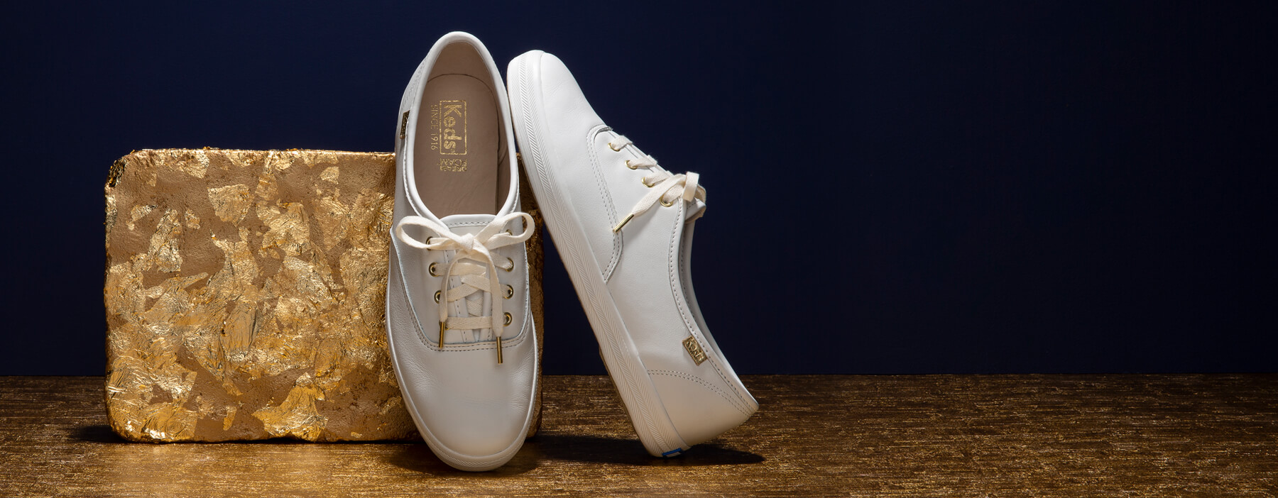 White, leather shoes with gold eyelets and shoelace tips.
