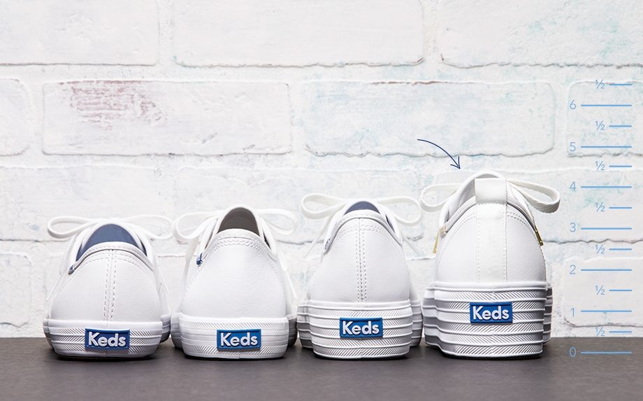 Shoes lined up against a white brick wall, being measured against each other