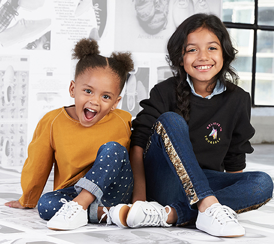 Two kids, grinning like crazy. They are super pumped about their kicks!