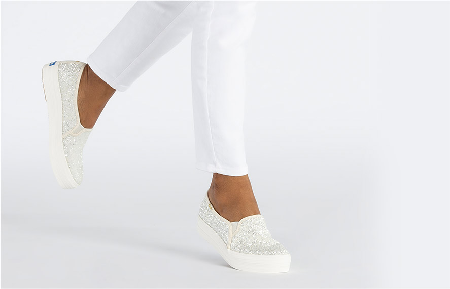 Woman dancing or jumping with white glitter shoes.