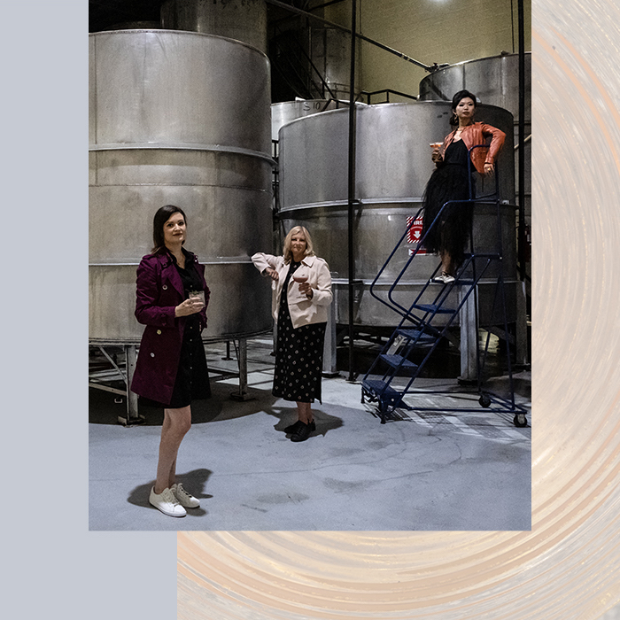 Three women in a brewery holding drinks