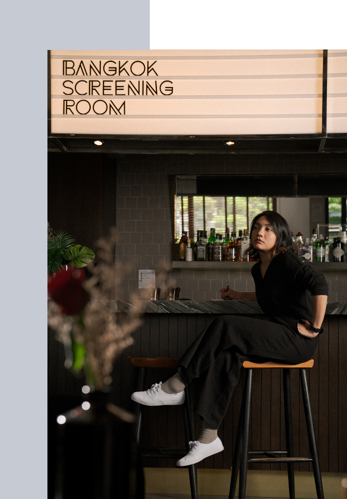 Rose Aksornsawang sitting on a stool beneath a sign that reads 'Bangkok Screening Room'