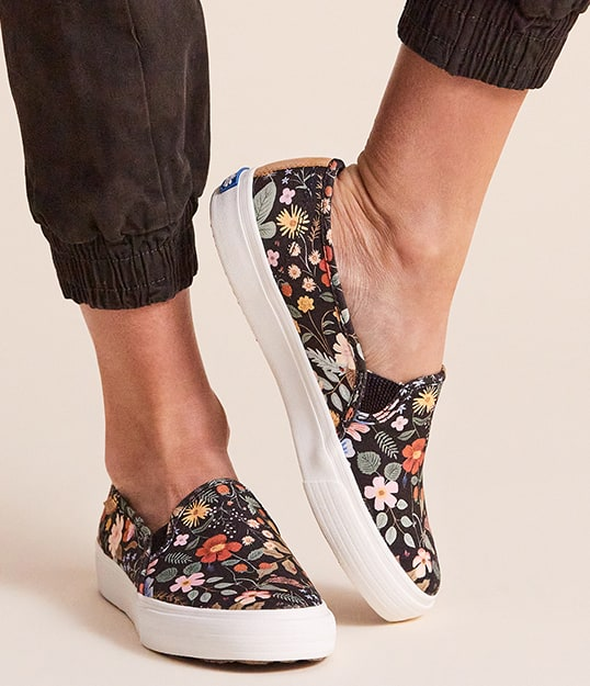 Person wearing Keds sneakers with flowers on them.