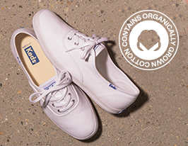 Keds organic cotton shoes on sand.