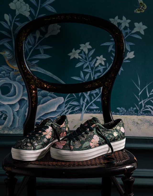 A beautiful pair of Keds flowery shoes on a chair.