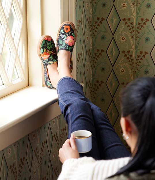 A person relaxing with thier feet up, wearing flowery keds shoes.