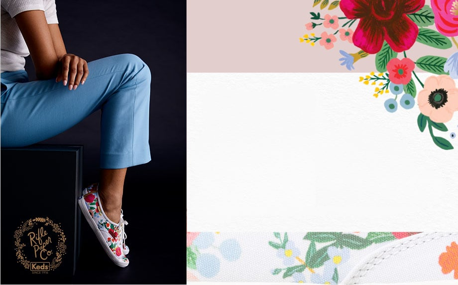 A woman sitting on a box, wearing a pair of Keds x Rifle Paper Co. Champion Wild Rose shoes.