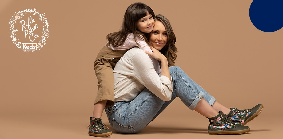 Woman sitting on the floor with a small girl hugging her, both wearing Keds shoes