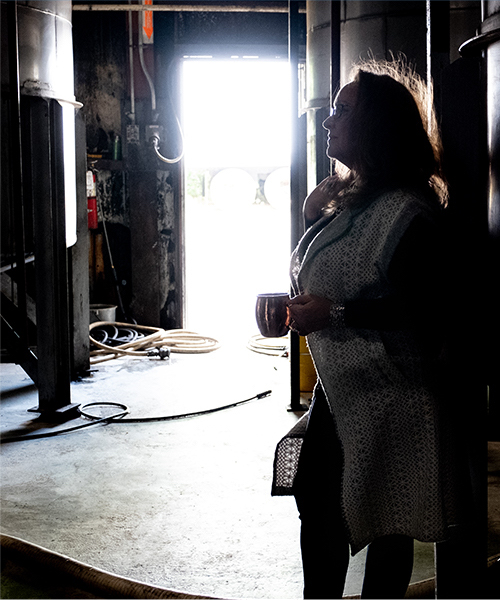 a woman holding a drink and standing in a back room