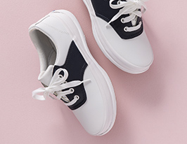 A pair of girl shoes on a pink background.