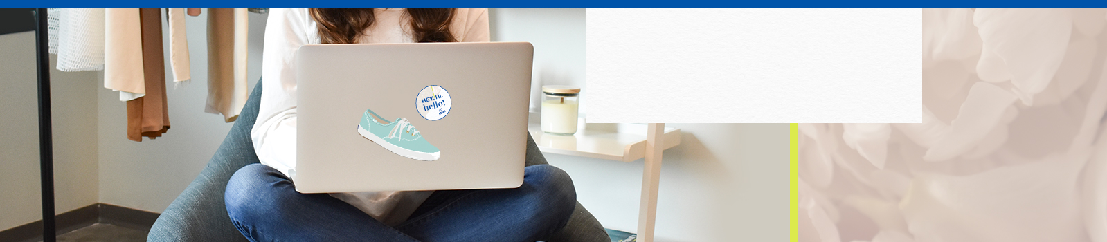 Female sitting in a chair, cross-legged, ordering stickers from Keds on her laptop.