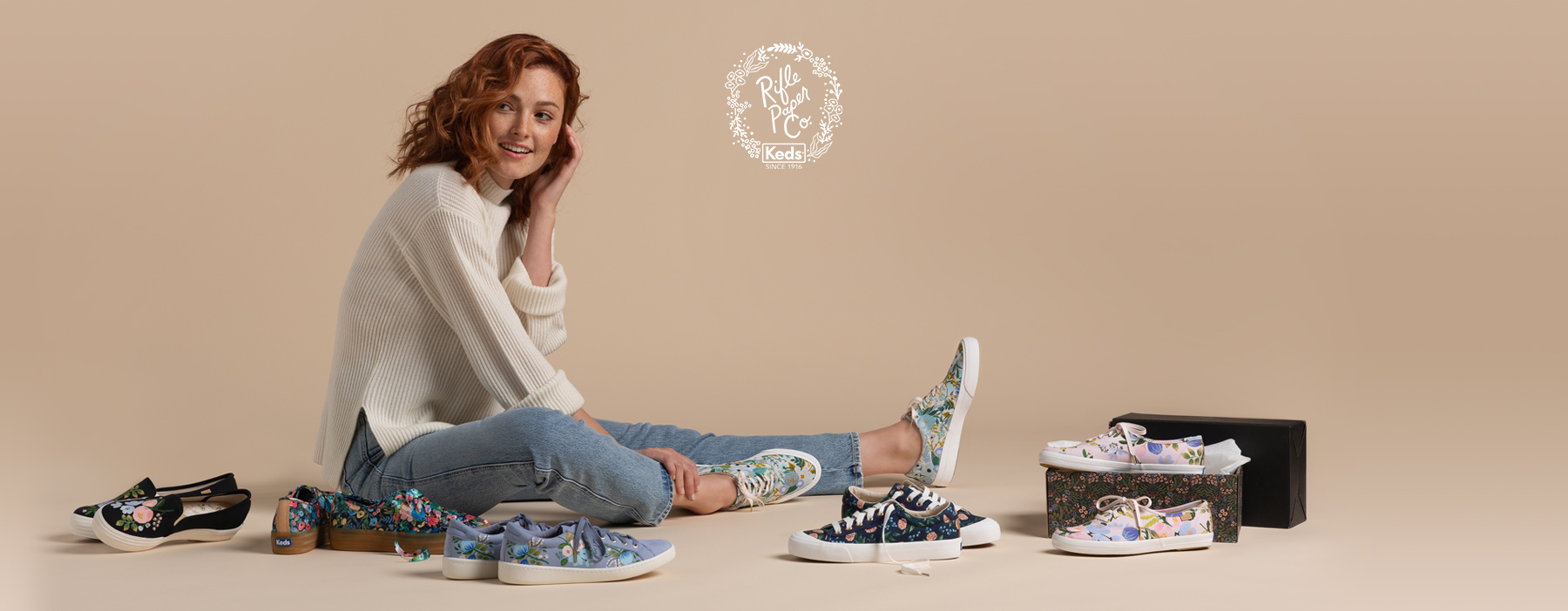 Red-haired woman sitting on the floor sorrounded by Rifle Paper Co print Keds.