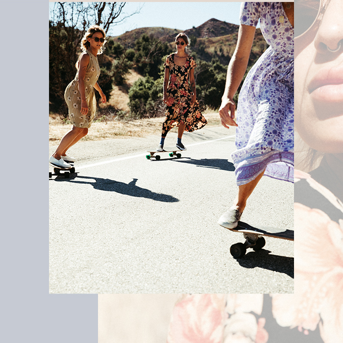Three women wearing dresses and riding skateboards