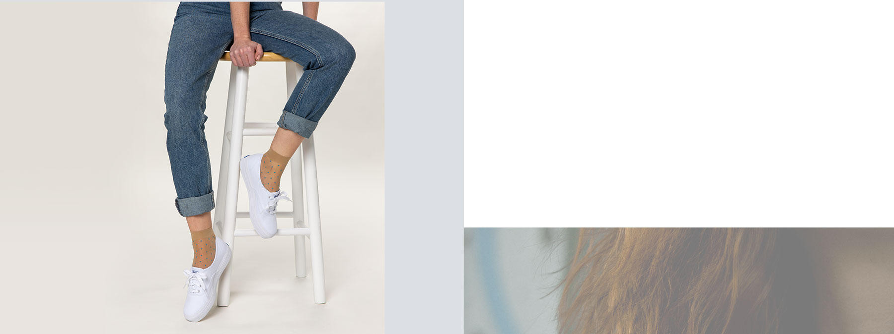 A woamn sitting on a stool in jeans and white keds cushioned platform sneakers.