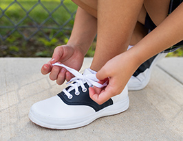 Tying a pair of kids shoes on a sidewalk.