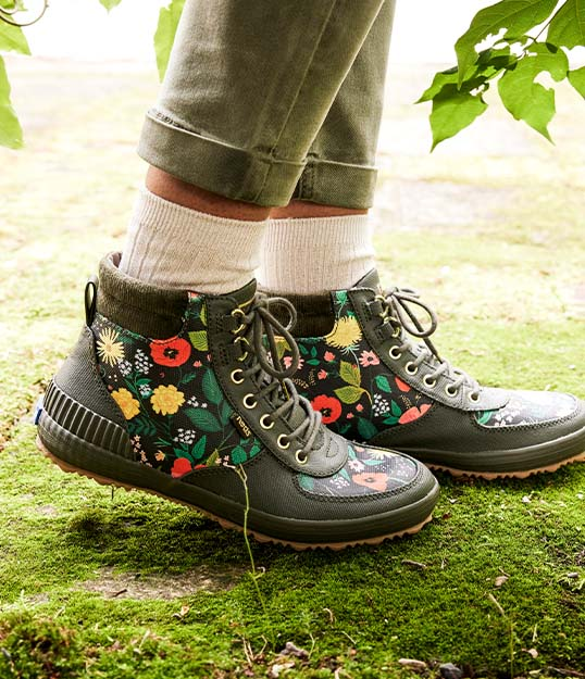 Person standing on grass, wearing flowery Keds boots.